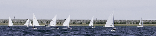 The upstream side of Fort Peck Dam in background, 2016 Can-Am Sailing Regatta in foreground